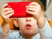 Junge, der das Frühstück essend spielt mit Handy geifert Stockfotografie
