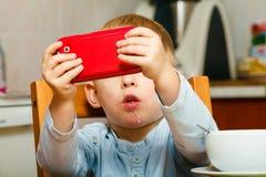 Junge, der das Frühstück essend spielt mit Handy geifert Lizenzfreies Stockfoto