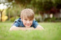 Junge, der in das Gras legt Stockbilder