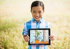 Junge, der das Haus mit Tablette zeigt Lizenzfreies Stockfoto