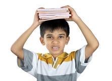 Junge, der das Lehrbuch mit Ausdruck hält Lizenzfreies Stockbild