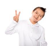Junge, der das Zeichen des Sieges und der Friedenshand zeigt Stockbild