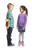 Junge, der dem Mädchen rosafarbene Blume gibt Lizenzfreies Stockfoto