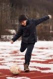 Junge, der den Ball im Winter tritt Lizenzfreies Stockfoto