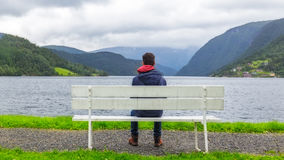 Junge, der den Fjord in Ulvik, Norwegen betrachtet Lizenzfreie Stockfotografie