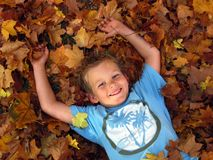 Junge, der in den Herbstblättern spielt Stockfotos