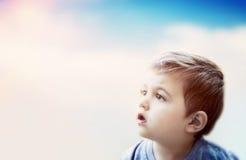 Junge, der den Himmel mit überraschtem Ausdruck betrachtet Kinderphantasie Lizenzfreies Stockfoto