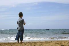 Junge, der den Ozean betrachtet Stockbild