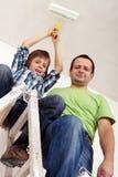 Junge, der den Raum mit seinem Vater malt Stockbild