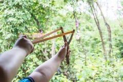 Junge, der den Riemen-Schuss, Gummistreifen in Erwartung des Katapult-Schusses zurückziehend hält stockfotos