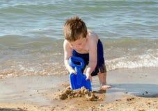 Junge, der in den Sand gräbt stockfoto