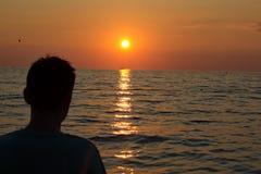 Junge, der den Sonnenuntergang auf dem Ozean aufpasst Stockfoto