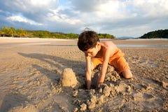 Junge, der den Spaß draußen spielt im Sand durch den Strand bei Sonnenuntergang hat Stockbilder