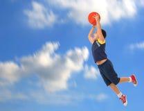 Junge, der den springenden und fliegenden Basketball spielt Lizenzfreie Stockfotos