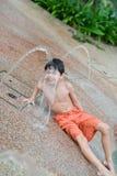 Junge, der den Wasserbrunnen genießt Stockbild