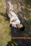 Junge, der in der Hängematte schläft Lizenzfreies Stockfoto