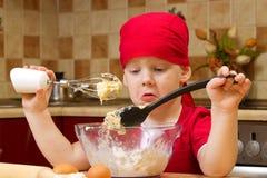Junge, der an der Küche mit Backentorte hilft Stockfotografie