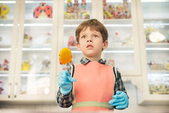 Junge, der an der Küche mit Lutscher steht Lizenzfreie Stockfotos