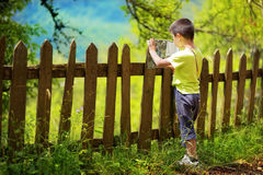 Junge, der in der Karte nahe bei dem Dorfzaun auf einem fantastischen sunn schaut Stockbild