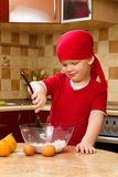 Junge, der an der Küche mit Backentorte hilft Lizenzfreie Stockfotos