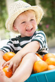 Junge, der in der Schubkarre gefüllt mit Orangen sitzt Lizenzfreie Stockfotografie