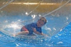 Junge, der in der Wasserkugel liegt Lizenzfreies Stockfoto