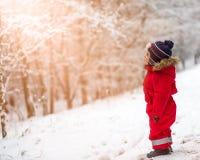 Junge, der in der Winterlandschaft spielt Recht kleines Mädchen auf Spielplatzhintergrund Lizenzfreies Stockbild