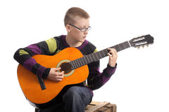 Junge, der die accoustic Gitarre spielt Lizenzfreie Stockbilder