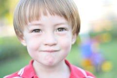 Junge, der die beißende Lippe der Kamera betrachtet stockbilder