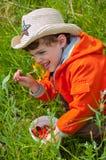 Junge, der die Blume mit freudiger Erregung riecht Stockbild