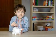 Junge, der die 1 Euromünze zu seinem Sparschwein setzt Lizenzfreies Stockfoto