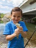 Junge, der die Fische zeigt, die er fing Stockfotos