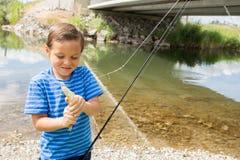 Junge, der die Fische zeigt, die er fing Stockbilder