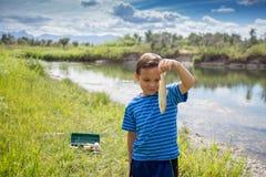 Junge, der die Fische zeigt, die er fing Lizenzfreies Stockbild