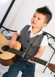 Junge, der die Gitarre der natürlichen Größe knirscht die Zähne spielen Musik staut Stockbilder