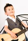 Junge, der die Gitarre der natürlichen Größe knirscht die Zähne spielen Musik staut Lizenzfreies Stockbild
