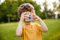 Junge, der die Kamera steht im Park hält Lizenzfreie Stockbilder