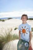 Junge, der die Plastiktasche gefüllt mit Abfall auf Strand trägt Lizenzfreies Stockfoto