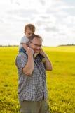 Junge, der die Schultern seines Vaters reitet Stockfotografie