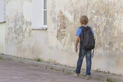 Junge, der in die Straße mit seinem Rucksack geht Rückseitige Ansicht Leutebildung, Schule, Reise, Freizeitkonzept Lizenzfreie Stockfotografie