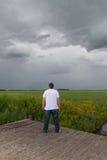 Junge, der die Sturmwolken aufpasst Stockbilder