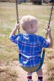 Junge, der draußen auf einem Swingset spielt stockfotos