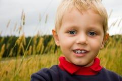 Junge, der draußen auf Feld lächelt Stockbild