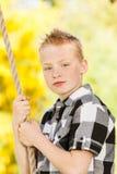 Junge, der draußen ein Seil im Garten erfasst Stockfotos