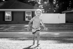 Junge, der draußen im Yard spielt lizenzfreie stockfotos