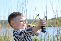 Junge, der draußen Riemen-Schuss durch See zielt lizenzfreies stockbild