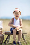 Junge, der draußen sitzt Stockfoto