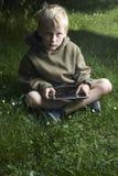 Junge, der draußen Spiel mit Tabletten-PC spielt Lizenzfreie Stockbilder