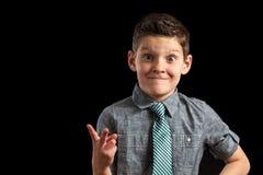 Junge, der dummes Gesichts-und Friedenszeichen macht stockbild