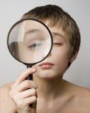 Junge, der durch das Objektiv schaut stockfoto